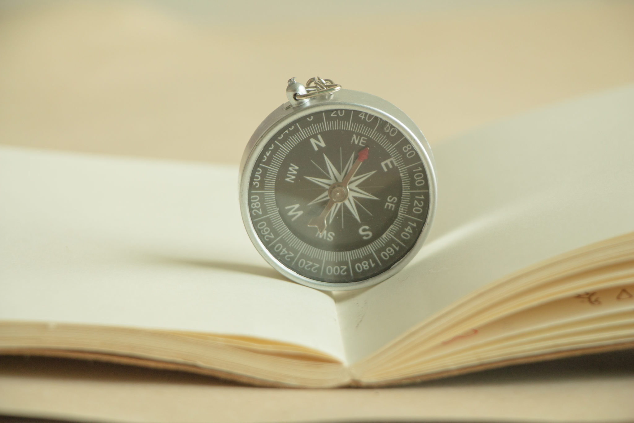 Close-Up Of Compass In Book On Table
