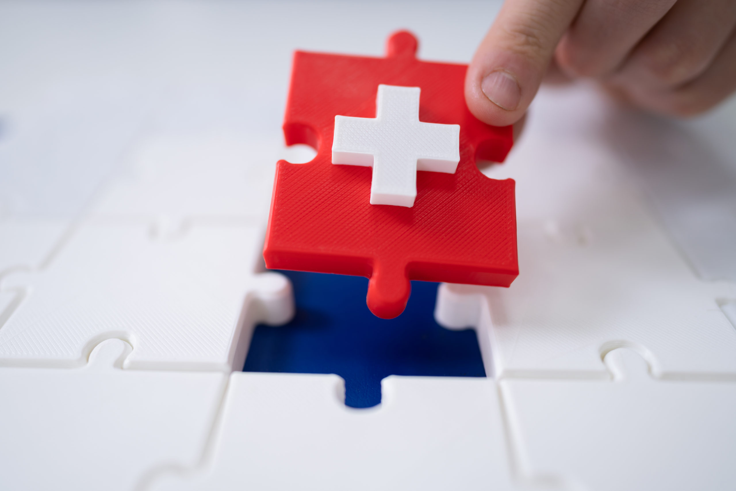 Man's Hand Solving Jigsaw Puzzle